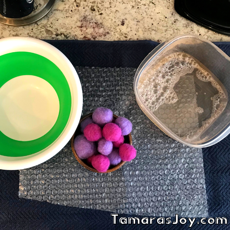 Showing a bowl and dry felted balls next to hot soapy water